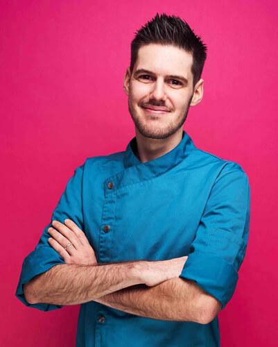 """Martin ist als gelernter Koch zu uns gestoßen und kann nun zeigen, wie süß er wirklich kochen kann. Meistens experimentiert er mit neuen Rohstoffen oder zeigt in der Showküche unseren Kursteilnehmern, wie man Zucker zu Motivbonbons verwandelt. Als passionierter Kölner Haie Fan ist sein Lieblingsprodukt natürlich der """"KEC Sharky Lutscher""""."""